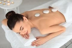 Young woman undergoing hot stone therapy in spa Royalty Free Stock Photo