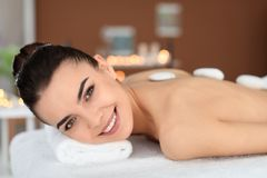 Young woman undergoing hot stone therapy. In spa salon Stock Image
