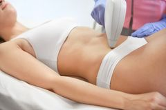 Young woman undergoing laser epilation procedure. In beauty salon stock photo