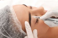 Young woman undergoing procedure of permanent eyebrow makeup in tattoo salon. Closeup stock photo