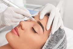 Young woman undergoing procedure of permanent eyebrow makeup in tattoo salon. Closeup stock images