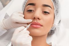 Young woman undergoing procedure of permanent lip makeup in tattoo salon. Closeup stock photo