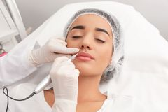 Young woman undergoing procedure of permanent lip makeup. In tattoo salon stock image