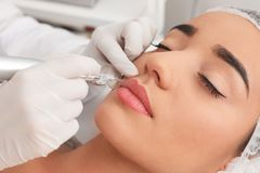 Young woman undergoing procedure of permanent lip. Makeup in tattoo salon, closeup royalty free stock images