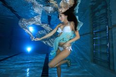 Young woman underwater in the pool. Posing with silver foulard Royalty Free Stock Photography