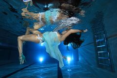 Young woman underwater in the pool. Posing with silver foulard Royalty Free Stock Photos