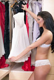 Young woman in underwear choosing clothes Stock Images