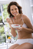 Young woman in underwear eating breakfast, smiling, portrait Stock Photos