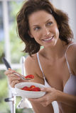 Young woman in underwear eating strawberries and cereal, smiling Royalty Free Stock Photo