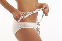 Young woman in underwear with measuring tape Stock Photography
