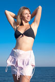 Young woman undresses on seashore Stock Photos