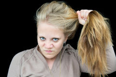 Young woman unhappy with her hair. Young woman showing their displeasure with her hair by tearing at it Stock Images