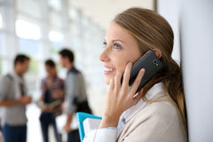 Young woman at university hall talking on phone Royalty Free Stock Photography
