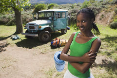 Young woman unloading parked jeep at start of camping holiday, holding sleeping mat, smiling, portrait Royalty Free Stock Images