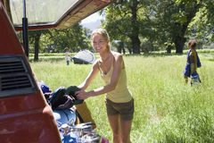 Young woman unloading parked SUV in woodland clearing on camping trip, side view, smiling, portrait Stock Images
