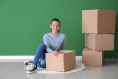 Young woman unpacking box indoors. Moving into new house stock photo