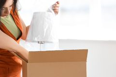 Young woman unpacking box indoors. Moving into new house stock images
