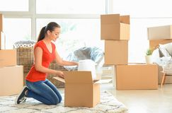Young woman unpacking box indoors. Moving into new house stock photos