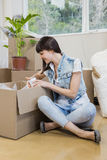 Young woman unpacking carton boxes Royalty Free Stock Image