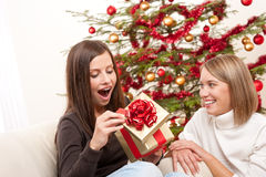 Young woman unpacking Christmas gift. Surprised Royalty Free Stock Photography