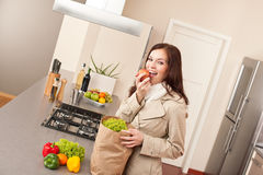 Young woman unpacking shopping bag in kitchen Royalty Free Stock Images