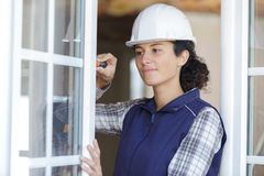 Young woman unscrews fixing screws window handle. Young woman unscrews the fixing screws of the window handle stock images