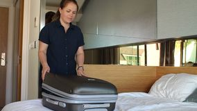 Woman unzips a suitcase on a bed in a hotel. Packing Luggage in a suitcase. A young woman unzips a suitcase in a room on a bed in a hotel. The girl disassembles stock video footage