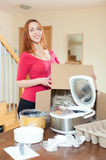 Young woman upacking electric slow cooker in kitchen at home Royalty Free Stock Image