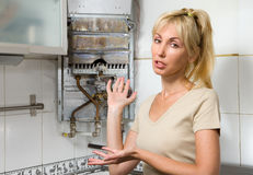 The young woman is upset by that the gas water hea Stock Photo