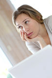 Young woman with upset look in front of laptop Royalty Free Stock Photo