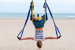 Young woman upside down doing anti-gravity aerial yoga or fly-yoga in hammock on sea background Stock Photography