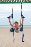 Young woman upside down doing anti-gravity aerial yoga or fly-yoga in hammock on sea background Royalty Free Stock Photography