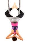 Young woman upside down doing anti-gravity aerial yoga. On white background stock image