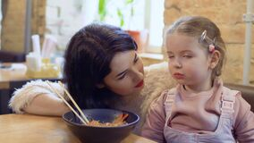 Young woman urges her little daughter to try a korean delicious noodles. Young woman urges her little daughter to try korean delicious noodles. Happy family is stock footage