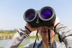 Young woman use of the binocular Royalty Free Stock Images