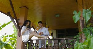 Young woman use cell smart phone sitting on balcony, man bring juice, happy couple talking on summer terrace stock video