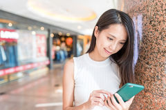 Young Woman use of mobile phone in shopping mall royalty free stock photos