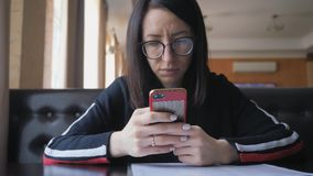 Young woman use mobile phone while sitting in comfortable coffee shop during work break, charming happy female reading. Fashion news on cell telephone during stock video footage