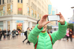 Young woman use smartphone taking photo on shopping street Royalty Free Stock Images