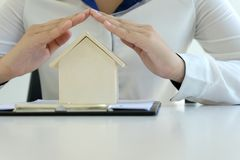 Young woman use two hand to protect house model. Concept home insurance Stock Image