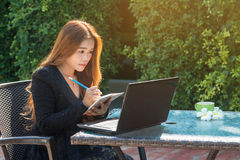 Young woman used a pencil. To write notes with laptop Royalty Free Stock Images