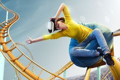 Young woman used Virtual reality helmet VR. She see Roller coaster park. Young woman used Virtual reality helmet VR. She see Roller-coaster park stock photography