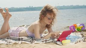 Young woman uses computer tablet on the beach, river bank. A young woman in pink clothes, in sunglasses lying on the sand and using a computer tablet, the beach stock video