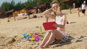 Young woman uses computer tablet on the beach, river bank. A young woman in pink clothes, in sunglasses siting on the sand and using a computer tablet, the beach stock footage