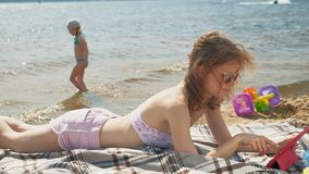 Young woman uses computer tablet on the beach, river bank. A young woman in pink clothes, in sunglasses lying on the sand and using a computer tablet, the beach stock video footage