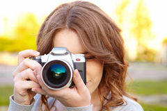 Young woman uses digital slr photocamera. Royalty Free Stock Photography