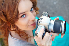 Young woman uses digital slr photocamera. Stock Images