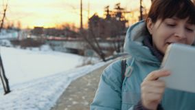 A young woman uses a digital tablet outdoors in winter. Young happy woman in gray top clothes enjoys a digital tablet outdoors against a background of the stock video