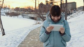 A young woman uses a digital tablet outdoors in winter. Young happy woman in gray top clothes enjoys a digital tablet outdoors against a background of the stock video footage