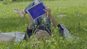 Young woman uses digital tablet relaxing on blanket in park. Young woman is relaxing on blanket in park and uses digital tablet. The female enjoys warm weather stock video